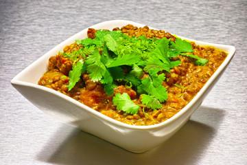 Moong Dahl, indian vegetarian lentil soup in white bowl.
