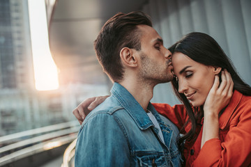 Side view glad female kissing smiling girlfriend in forehead during rest outside. She gesticulating hands while embracing him
