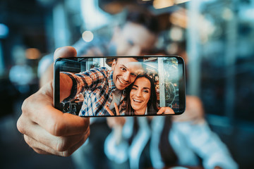 Portrait of cheerful female and positive man watching at camera of contemporary phone while spending time together. Glad girl gesticulating hand