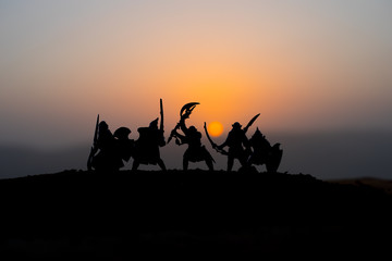 Medieval battle scene on sunset. Silhouettes of fighting warriors on sunset background.