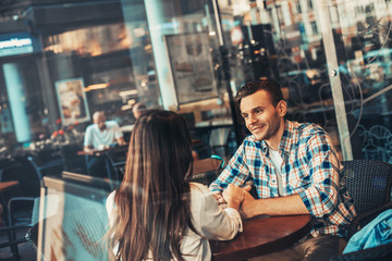 Positive male holding arm of woman while sitting at table in cozy cafe. Communication of glad couple concept