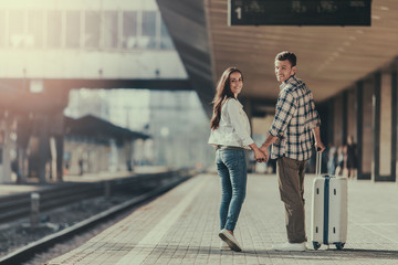 Full length portrait of cheerful female speaking with glad man while holding arms together. They walking on platform. He keeping baggage
