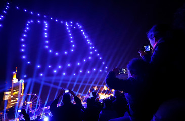 People use their smartphones to take pictures of the skyline illuminated by drones during an art installation celebrating the opening of the re-built old town in Frankfurt