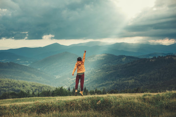 Panoramic view of mountains with an enthusiastic young woman expressing her joy on the hills