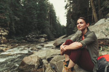 Friendly young woman sitting on the rocks of the mountain river while enjoying beautiful views