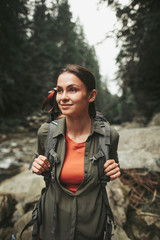 Pleasant young woman standing in the wood while traveling with pleasure