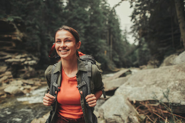 Cheerful attractive woman traveling near mountain river while spending weekend with pleasure