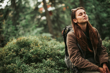 I feel healing energy. Portrait of serene girl with closed eyes enjoying atmosphere of coniferous wood