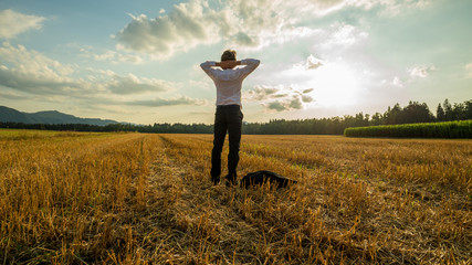 Businessman standing relaxed in harvested field
