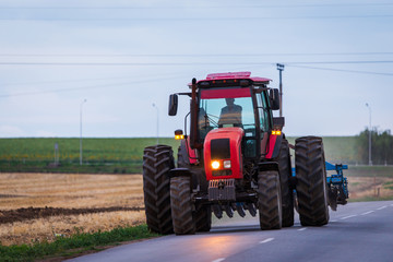Agricultural tractor moving on the asphalt road after working in field Wall mural