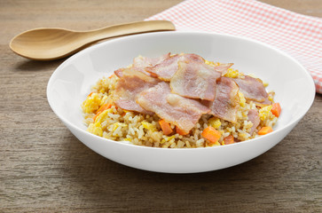 fried rice with bacon in a ceramic plate on wooden table, close up. homemade style food concept.