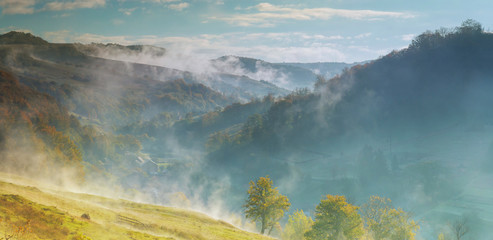 Beautiful misty morning in fog and cloud mountain valley landscape
