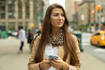 Young woman in city walking using cell phone