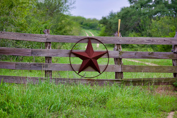 Texas rustic star on countryside side wooden fence, with road to the house slowly dissolving in the background.