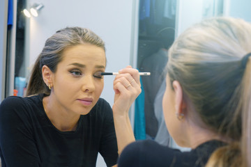 Woman doing makeup, looking in the mirror. Makeup in the daytime is prepared before going to a party.