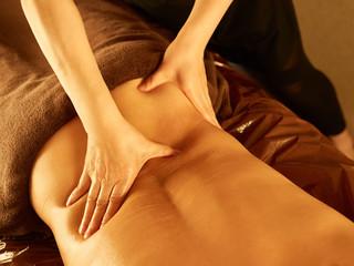 薄暗いメンズエステサロンで腰の指圧を受ける男性