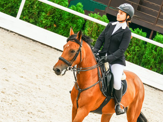 Beautiful girl on sorrel horse in jumping show, equestrian sports. Light-brown horse and young woman in uniform going to jump.