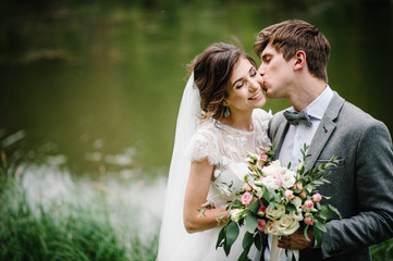 Portrait of young wedding couple kissing at nature. Newlyweds.