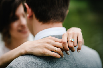 View of hands with wedding rings. Wedding day. Portrait of an attractive groom hugs bride on nature in the park. Happy and joyful moment. Romantic couple of newlyweds.