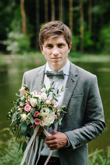 The attractive groom in a suit and bow tie, jacket, is standing and holding in hand bouquet of pink flowers and greens with ribbon at nature on the in the garden park.