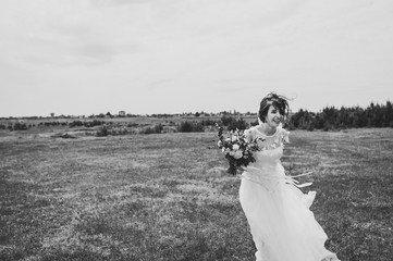 Young beautiful bride in an elegant dress is standing and holding bouquet of flowers and greens with ribbon on nature in the park. Black and white photo.