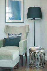 Black and white pillow on velvet louge chair at corner in living room with floor lamp
