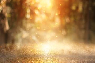 Fototapete - blurred abstract photo of light burst among trees and glitter golden bokeh lights.
