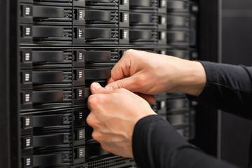 Male IT Engineer Adjusting Hard Drives In SAN At Datacenter