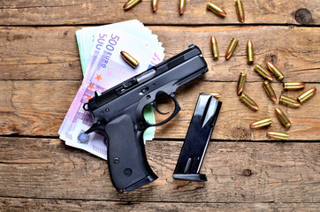 Top view of 9mm pistol - handgun, bullets, euro banknotes and magazine on old wooden table