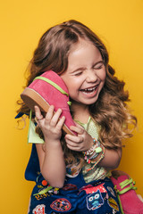 Young fashion model on an orange background, fashion kid