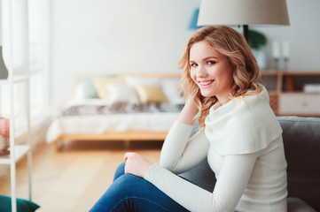 young beautiful woman enjoying time at home, sitting on cozy couch in warm sweater. Happy life, mental health, balance and restore concept