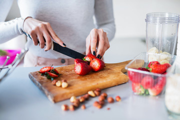 Close up of woman hands cutting strawberries on cutting board.
