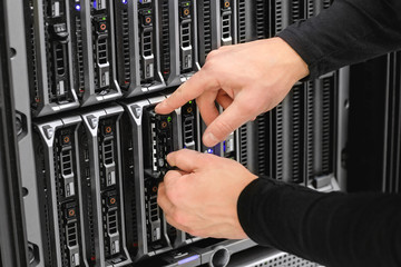 Male Technical Consultant Installing Blade Server In SAN At Data