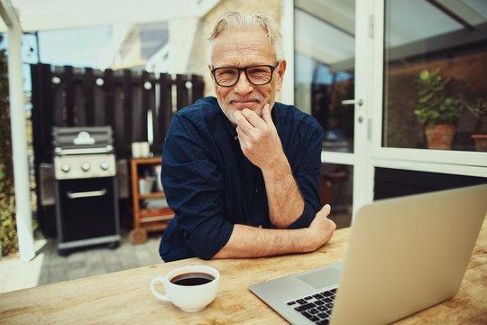 Smiling senior man sitting outside working on a laptop