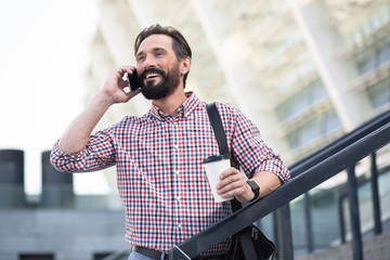 Waist up of an optimistic handsome man talking on mobile phone