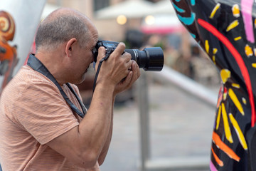 A man with a photo camera photographed on the street.