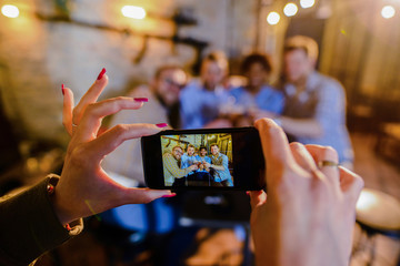 Close up of females hands taking a picture of four happy male friends drinking in a bar.