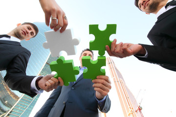 Business people assembling jigsaw puzzle