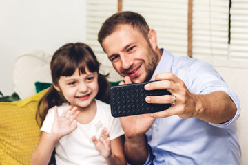 Father with little daughter having fun and taking selfie together with smartphone while sitting on the sofa at home.Love of family and concept