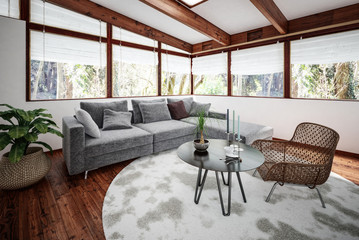 Sitting room with chair and sofa next to plant