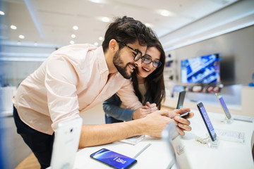 Cute young couple in electronic store testing some new telephones. Searching for ideal equipment.