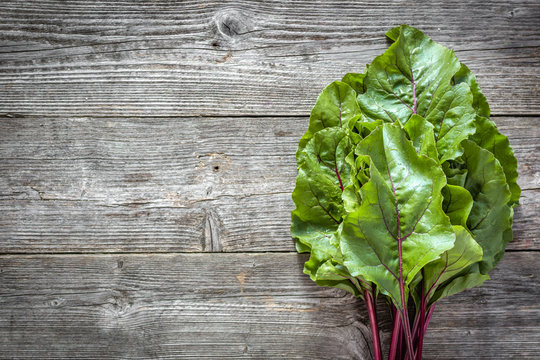 Farm fresh vegetables - green leaves of beet, bunch on wooden background