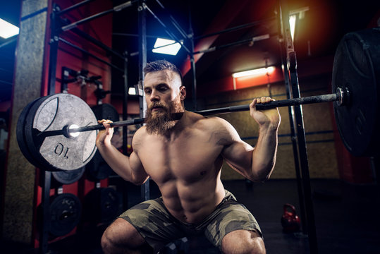 Bearded strong sporty man lifting heavy weight in dark room.