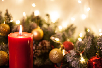 Christmas candles on the background of branches of a Christmas tree and glowing garlands