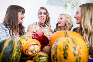 Young and beautiful woman posing funny and scary while toasting with her best friends during Halloween costume party