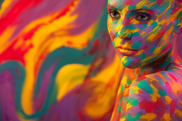 Portrait of the bright beautiful girl with brush, art colorful make-up face art and bodyart