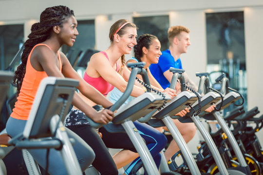 brunette beautiful woman smiling while cycling on a modern fitness bicycle during group spinning class at the gym