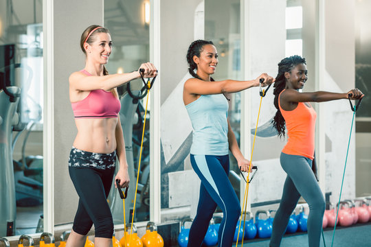 Full length of three fit and beautiful women standing up while exercising with fitness resistance bands during workout class for ladies at the gym