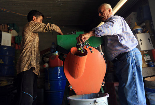 Gorgis, an Iraqi Christian wine maker, uses a grape squeezing machine invented by his son to squeeze grapes before filtering them and leaving them to ferment for 40 days in Dhiha village near Duhok