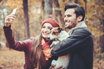 Woman and man with their dog on autumn walk taking a phone selfie posting it online on social media